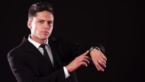 Il tipo aggrottante le sopracciglia indica all'orologio sul suo polso archivi video