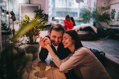Il tipo amoroso felice tiene la mano della sua amica che si siede alla tavola nel caffè e la esamina immagine stock