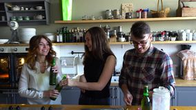 Il tipo apre le bottiglie ed il lough, beve le bottiglie del tintinnio e della birra con le ragazze sulla cucina video d archivio