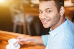 Il tipo arabo attraente sta rilassandosi in self-service Fotografia Stock