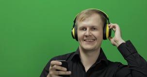 Il tipo ascolta musica in cuffie gialle senza fili e nei balli Schermo verde stock footage