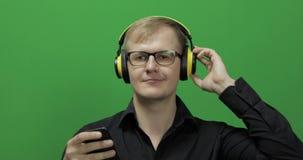 Il tipo ascolta musica in cuffie gialle senza fili e nei balli Schermo verde video d archivio