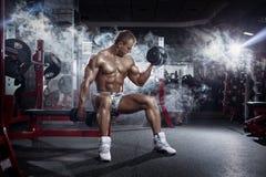 Il tipo atletico del culturista, esegue la stampa di esercizio con le teste di legno, Fotografia Stock Libera da Diritti
