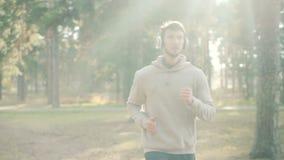 Il tipo attraente in maglietta felpata d'avanguardia sta correndo in cuffie d'uso del parco e sta ascoltando la radio da solo il  archivi video