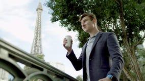 Il tipo attraente sta bevendo il caffè su un marciapiede con la torre Eiffel su un fondo archivi video