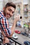 Il tipo attraente sta bevendo una tazza della bevanda Fotografie Stock Libere da Diritti