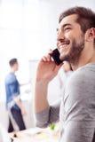 Il tipo attraente sta utilizzando il telefono per la comunicazione immagine stock