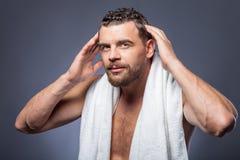 Il tipo barbuto bello è preoccuparsi della sua acconciatura immagine stock libera da diritti