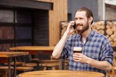 Il tipo barbuto bello sta comunicando sul telefono Fotografia Stock
