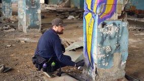 Il tipo barbuto dell'artista dei graffiti sta dipingendo sulla colonna in costruzione abbandonata con lo spruzzo della pittura de archivi video