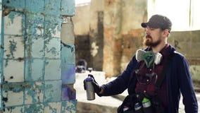Il tipo barbuto serio è concentrato sui graffiti della pittura vecchio sulla costruzione abbandonata della colonna interno sporco stock footage