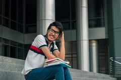 Il tipo bello sorride e si siede con i libri sulle scale Immagine Stock Libera da Diritti