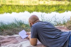 Il tipo calvo scrive in un taccuino nell'erba su una coperta e pensa ai sogni vicino al sole dell'estate del lago Fotografie Stock