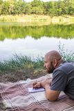 Il tipo calvo scrive in un taccuino nell'erba su una coperta e pensa ai sogni vicino al sole dell'estate del lago Fotografia Stock Libera da Diritti