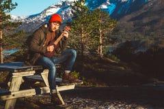 Il tipo che gioca la chitarra che si siede su una tavola di legno contro lo sfondo delle montagne, foreste e laghi, porta una cam immagini stock