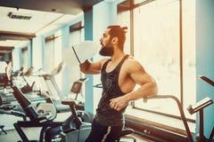 Il tipo che si rilassa dopo l'allenamento e l'acqua della bevanda o della tenuta da grande imbottiglia la palestra Fotografie Stock