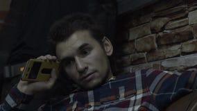 Il tipo che si siede sullo strato e che guarda intorno Un uomo riposa su un sofà con un telefono video d archivio