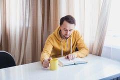 Il tipo che si siede vicino alla finestra alla tavola e legge Fotografie Stock