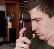 Il tipo chiuso il suo osserva ed attaccato lo smartphone al suo fronte, nella riflessione dei suoi occhi aperti e esamina la macc Immagini Stock Libere da Diritti