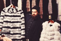 Il tipo con il fronte abile mostra le pellicce nel deposito di modo fotografie stock libere da diritti