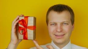 Il tipo con la sorpresa dentro la scatola sorride e esamina la macchina fotografica, sul fondo giallo della parete video d archivio