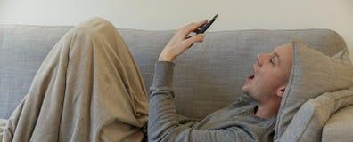 Il tipo con un freddo in un sofà utilizza un app medico immagine stock