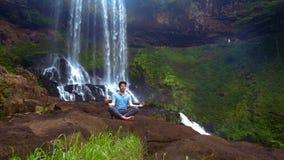 Il tipo concentrato medita in asana di padma di yoga alla cascata archivi video