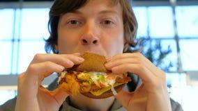 Il tipo concentrato tiene l'hamburger e mastica il primo piano video d archivio