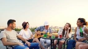 Il tipo creativo sta giocando la chitarra ed il suo gruppo multi-etnico degli amici sta cantando le bottiglie della tenuta con la archivi video