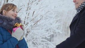 Il tipo dà alla ragazza un regalo Giovani coppie in un parco con il presente stock footage