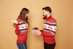 Il tipo dai capelli rossi dà il Natale che il regalo ad una ragazza sia è vestito in maglioni rossi che bianchi con i cervi e nei fotografia stock