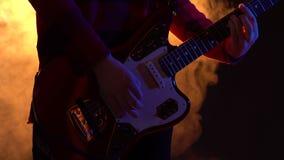 Il tipo dei pantaloni a vita bassa gioca la chitarra in scena in fumo video d archivio