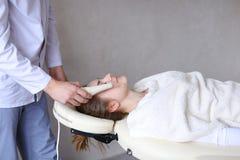 Il tipo del cosmetologo fa il massaggio di fronte speciale alla ragazza con cosmet Fotografie Stock