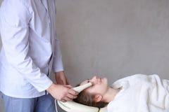 Il tipo del cosmetologo fa il massaggio di fronte speciale alla ragazza con cosmet Fotografia Stock Libera da Diritti