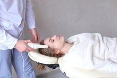 Il tipo del cosmetologo fa il massaggio di fronte speciale alla ragazza con cosmet Immagine Stock
