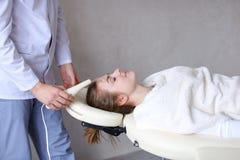Il tipo del cosmetologo fa il massaggio di fronte speciale alla ragazza con cosmet Fotografia Stock