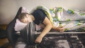 Il tipo del culturista di sport dorme con il bilanciere atletico, concetto dello stile di vita sano, resto atletico dell'uomo dop Immagine Stock