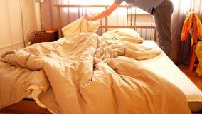 Il tipo del movimento lento prende i vestiti che fanno il letto matrimoniale nella mattina stock footage