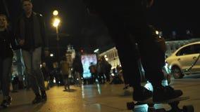 Il tipo del skateboarder in maglia con cappuccio nera guida sul marciapiede ammucchiato della città di notte stock footage