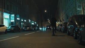 Il tipo del skateboarder in maglia con cappuccio nera guida sulla strada di città di notte stock footage