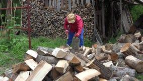 Il tipo dell'agricoltore taglia la legnaia a pezzi vicina di legno 4K stock footage