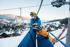 Il tipo dello sciatore che si siede alla seggiovia dello sci nel bello giorno e gira indietro Primo piano Concetto di corsa con g fotografia stock