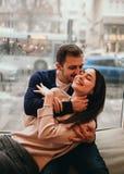 Il tipo di amore abbraccia la sua bella amica che si siede sul davanzale in un caff? accogliente fotografie stock libere da diritti