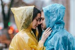 Il tipo di amore e la sua amica negli impermeabili stanno faccia a faccia sulla via nella pioggia immagine stock libera da diritti