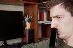 Il tipo distoglie lo sguardo tristemente, chiuso il rum con uno smartphone nero Fotografie Stock