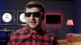 Il tipo divertente con la barba parla ed attivamente applaude in studio ammobiliato moderno scuro video d archivio