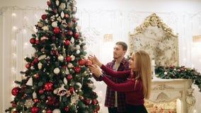 Il tipo e la ragazza decorano l'albero di Natale stock footage
