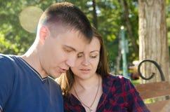 Il tipo e la ragazza delle coppie hanno letto le notizie fotografie stock libere da diritti