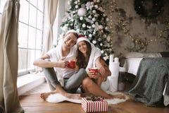 Il tipo e la ragazza felici in magliette e cappelli bianchi di Santa Claus si siedono con le tazze rosse sul pavimento davanti al immagine stock