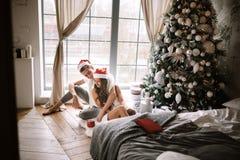 Il tipo e la ragazza felici in magliette e cappelli bianchi di Santa Claus sono sedentesi ed abbraccianti nella stanza sul pavime immagine stock libera da diritti